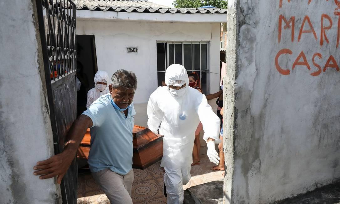 Trabalhadores do SOS Funeral retiram o corpo de Adamor Mendonça, de 75 anos, que segundo parentes morreu em casa após apresentar sintomas da Covid-19 e sem conseguir vaga nem oxigênio nos postos de saúde de Manaus Foto: BRUNO KELLY / REUTERS