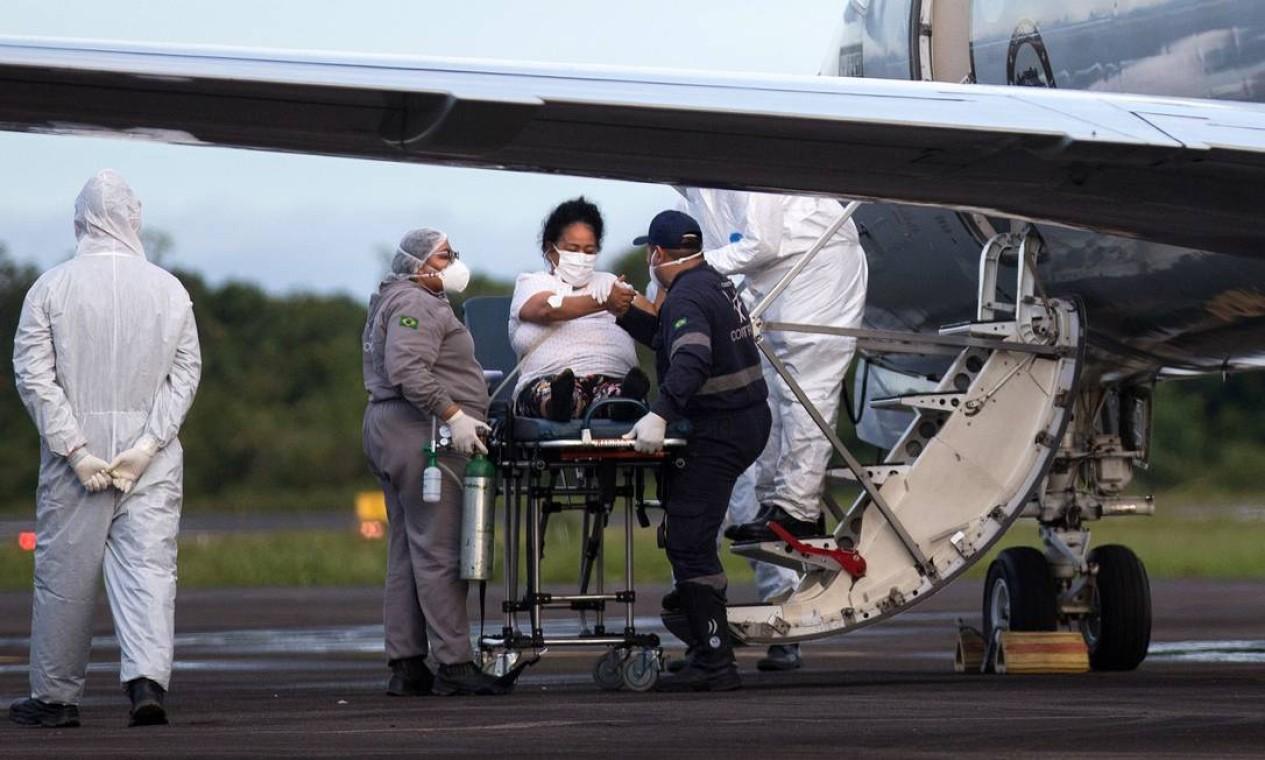 Paciente com Covid-19 é recebe atendimento de equipe médica no aeroporto de Ponta Pelada, em Manaus, antes de ser transferida para outro estado em avião militar Foto: MICHAEL DANTAS / AFP