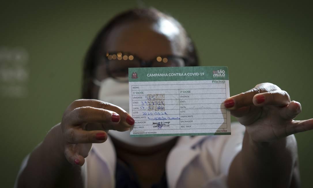 A enfermeira Mônica Calazans, de 54 anos, primeira vacinada contra Covid-19 no Brasil, exibe cartão de vacinação em São Paulo no último domingo (17) Foto: Edilson Dantas / Agência O Globo