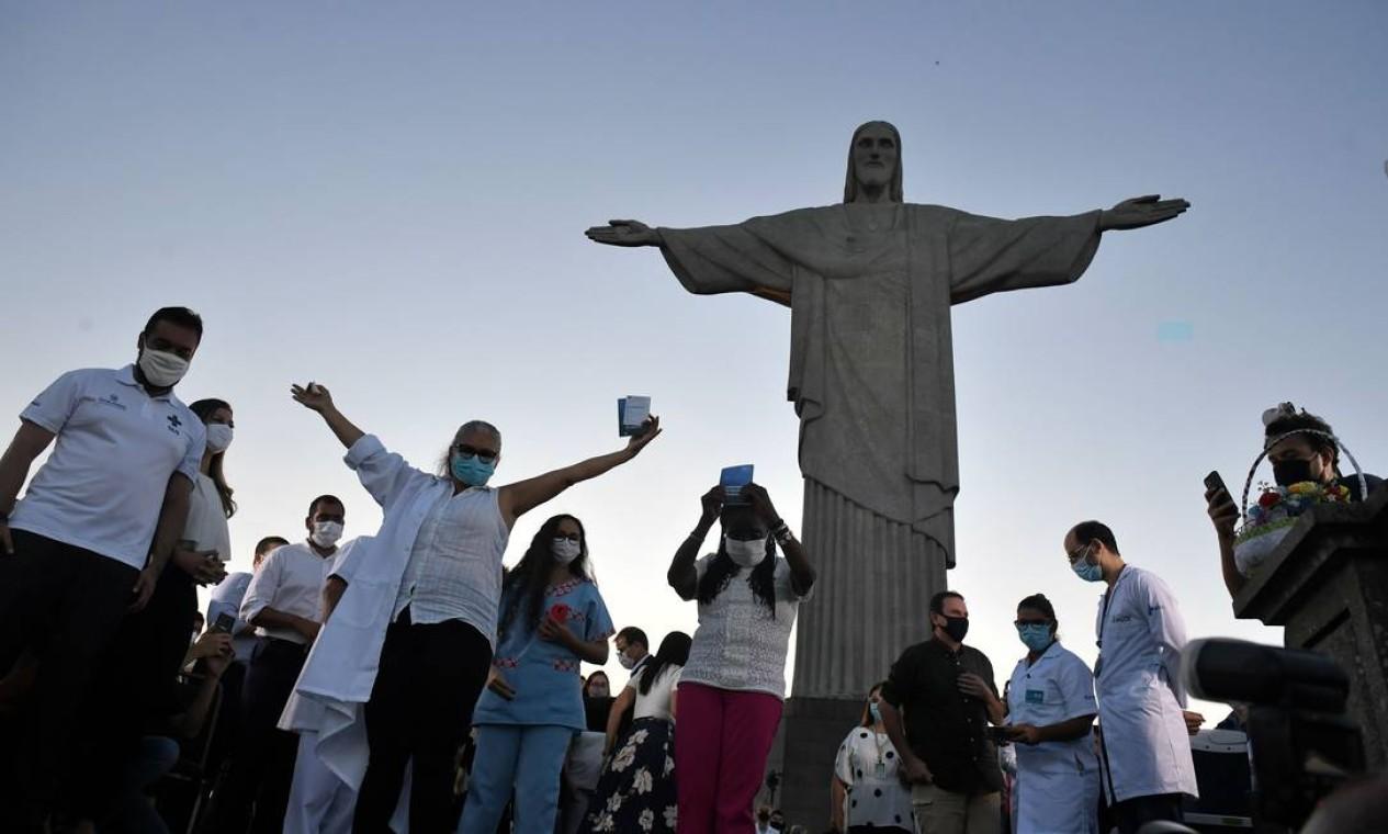 Dulcineia da Silva, 59, abre os braços para celebrar a imunização, diante da estátua do Cristo Redentoraes Foto: MAURO PIMENTEL / AFP