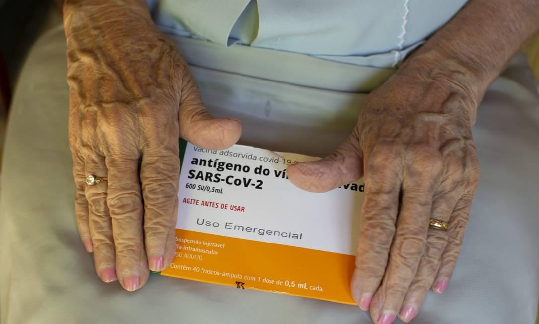 Dona Maria José, de 101 anos, exibe a caixa da CoronaVac: ela e mais cinco habitantes mais idosos de Rio das Flores foram vacinados Foto: Márcia Foletto / Agência O Globo