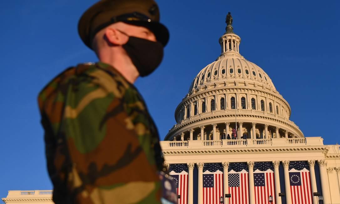 Vista do Capitólio decorado para a posse de Biden, no último por do sol em que os EUA foi governado por Donald Trump Foto: ANGELA WEISS / AFP