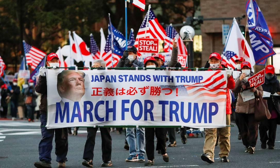 Apoiadores do presidente dos EUA, Donald Trump, seguram uma faixa enquanto marcham antes da posse do presidente eleito Joe Biden, no distrito de Ginza em Tóquio, Japão Foto: ISSEI KATO / REUTERS