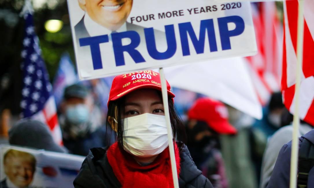 Japoneses apoiadores de Donald Trump usam máscara de proteção durante marcha em Tóquio Foto: ISSEI KATO / REUTERS