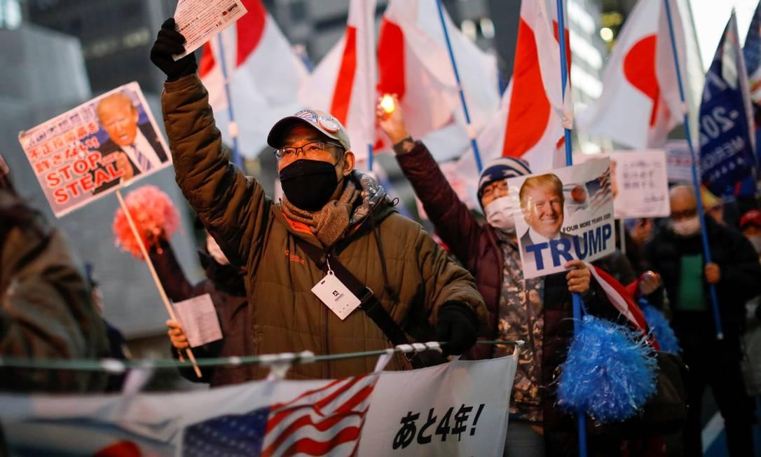 Com bandeiras do Japão e cartazes, grupo de japoneses marcha em apoio a Donald Trump pelas ruas do distrito de Ginza, na capital Tóquio Foto: ISSEI KATO / REUTERS
