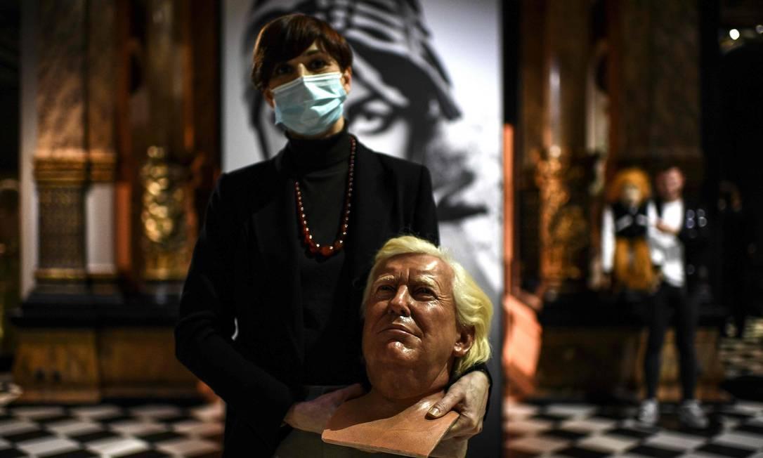 Funcionária do museu de cera Grevin segura escultura do ex-presidente Trump Foto: CHRISTOPHE ARCHAMBAULT / AFP