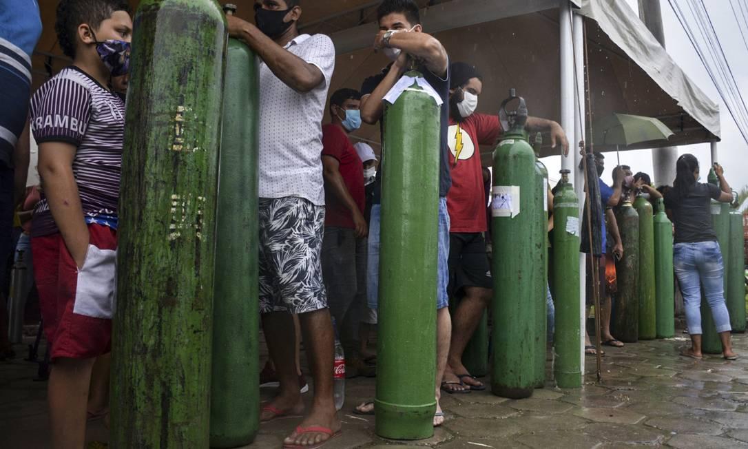 Parentes de pacientes com Covid-19 aguardam horas na fila para abastecer cilindros de oxigênio para tratamento das vítimas, em Manaus Foto: MARCIO JAMES / AFP