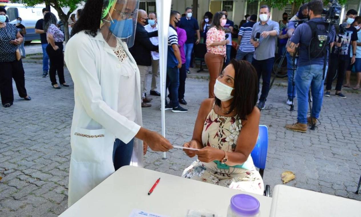 """A psicóloga e coordenadora do Programa de Saúde da Mulher Ruth Valentim recebe o cartãode vacinação após tomar a Coronavac nesta quarta-feira. Ela foi a primeira a ser imunizada em Japeri: """"É uma emoção que ultrapassa o campo profissional"""" Foto: Divulgação / Prefeitura de Japeri"""