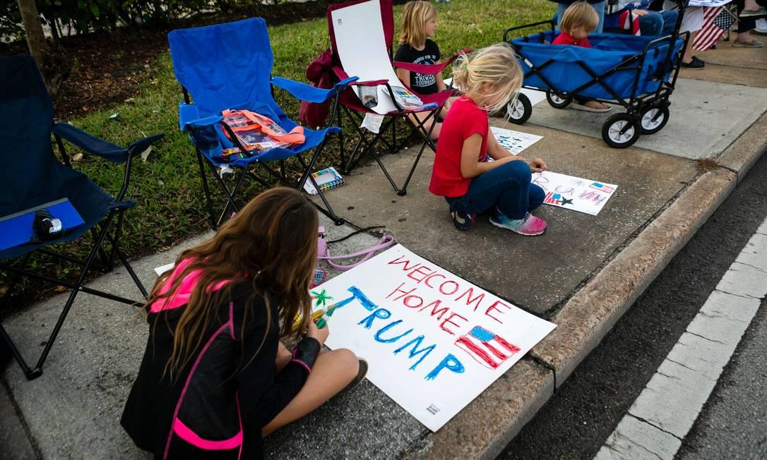 Filhos de apoiadores de Donald Trump pintam cartazes para ato durante a passagem da comitiva de Donald Trump, que decidiu não participar da posse do adversário político eleito, Joe Biden, e passará com a família em casa, no clube de golfe Mar-a-Lago em Palm Beach, Flórida Foto: EVA MARIE UZCATEGUI / AFP