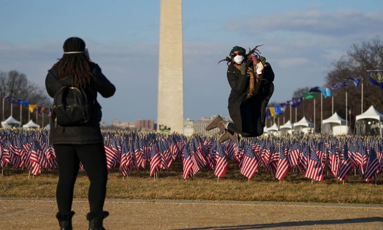 """Mulher pula para uma foto em frente ao """"Campo de bandeiras"""" e ao Monumento a Washington Foto: ALLISON SHELLEY / REUTERS"""