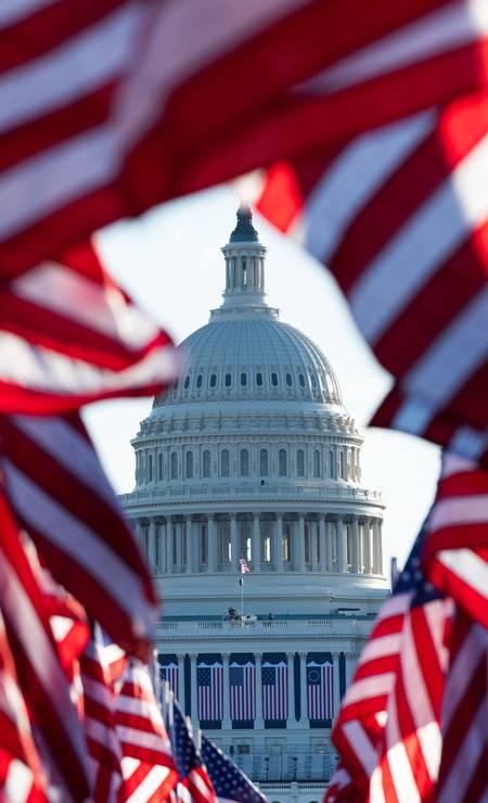 Capitólio é visto entre bandeiras dos EUA representando aqueles que não puderam comparecer à inauguração devido à Covid-19 antes da posse de Joe Biden Foto: ROBERTO SCHMIDT / AFP