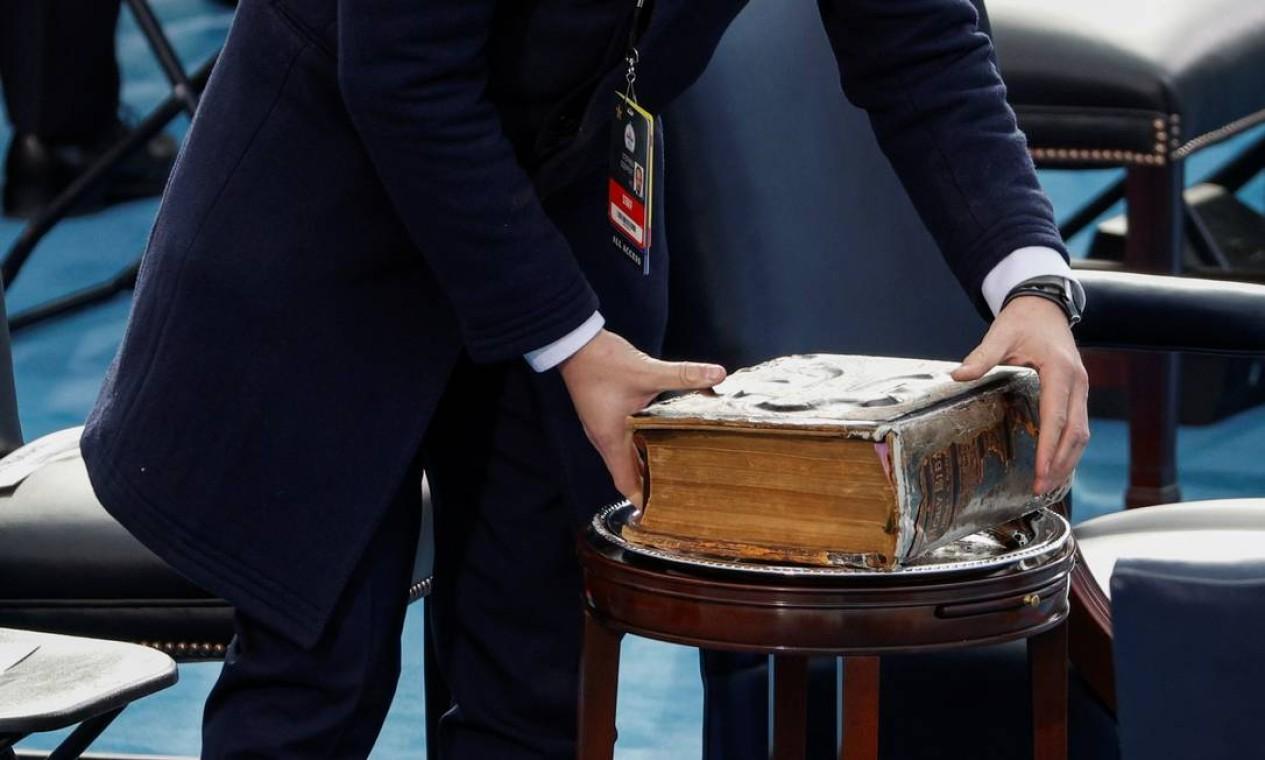 Um membro da equipe coloca a Bíblia em uma mesa antes da posse de Joe Biden Foto: BRENDAN MCDERMID / REUTERS