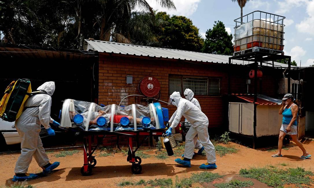 Profissionais de saúde transportam paciente de Covid-19, em Pretoria, na África do Sul Foto: PHILL MAGAKOE / AFP