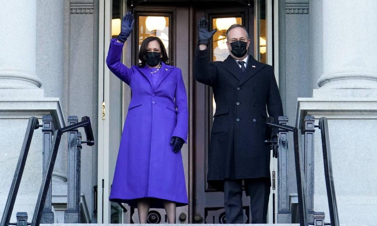 A vice-presidente, Kamala Harris, e seu marido, Douglas Emhoff, acenam da entrada do Eisenhower Executive Office Building, na Casa Branca. Casal repetiu a caminhada Biden até a sede do governo Foto: ERIN SCOTT / REUTERS