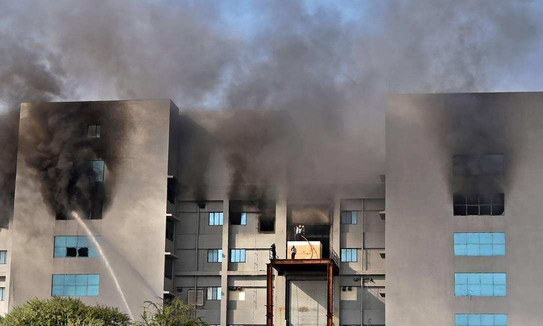 Bombeiros tentam controlar um incêndio no Serum Institute da Índia, em Pune. Serum Institute da Índia é maior fabricante mundial de vacinas. Segundo imprensa local, a produção dos imunizantes contra Covid-19 não foi afetada Foto: - / AFP