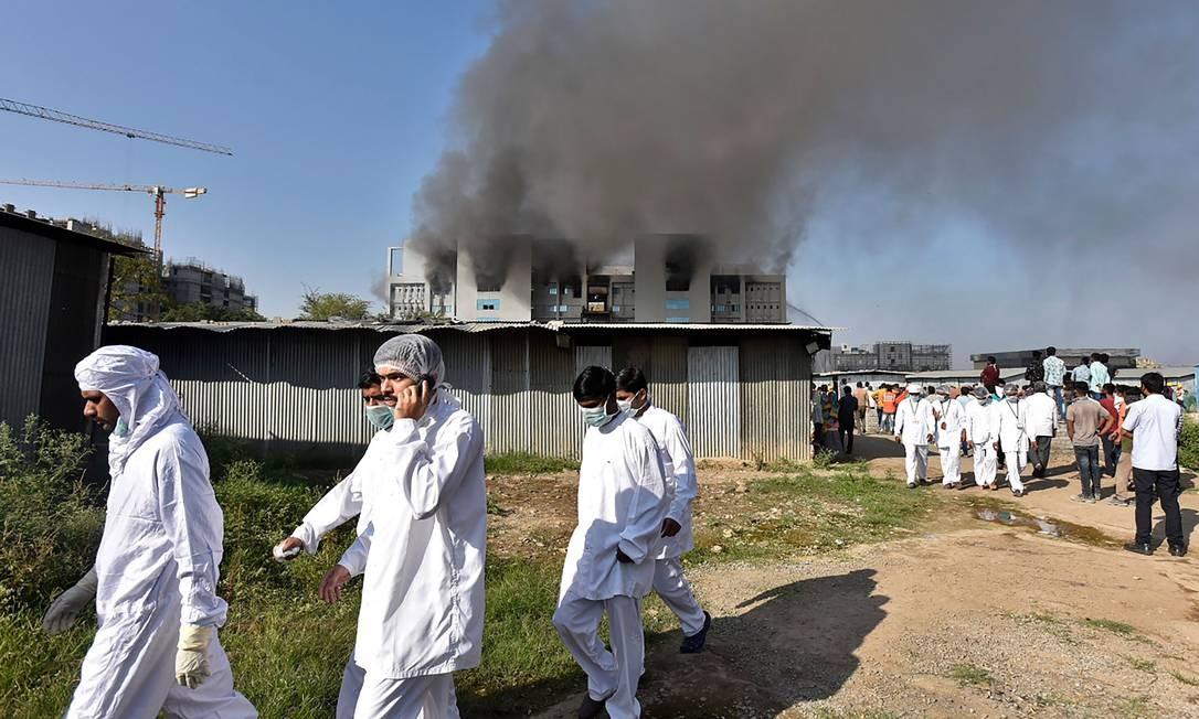 Trabalhadores usando equipamento de proteção caminham após um incêndio no Instituto Serum, da Índia Foto: - / AFP