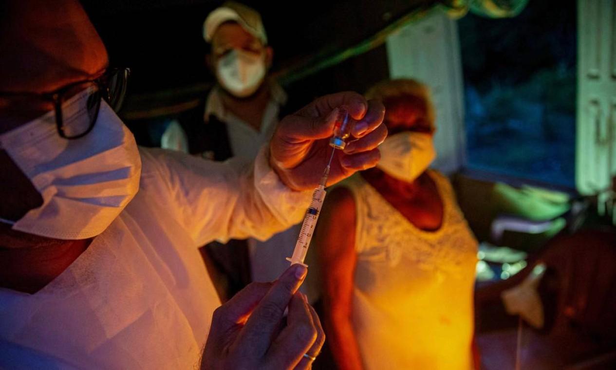 A profissional de saúde Raimunda Nonata, 70, se prepara para ser vacinada com a CoronaVac em sua casa, tornando-se a primeira quilombola imunizada no Quilombo Marajupena, no município de Cachoeira do Piriá, no Pará Foto: TARSO SARRAF / AFP - 19/01/2021