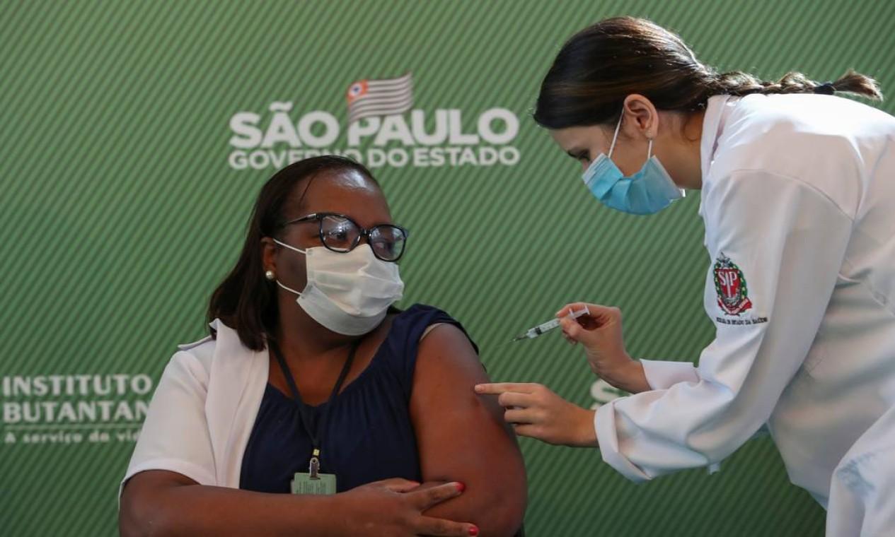 A enfermeira Mônica Calazans, 54 anos, recebe a primeira dose da vacina contra o novo coronavírus logo após a Anvisa aprovar seu uso de emergêncial, no Hospital das Clínicas de São Paulo. Mônica se tornou a primeira pessoa em território brasileiro a ser vacinada contra a Covid-19 Foto: AMANDA PEROBELLI / REUTERS - 17/01/2021