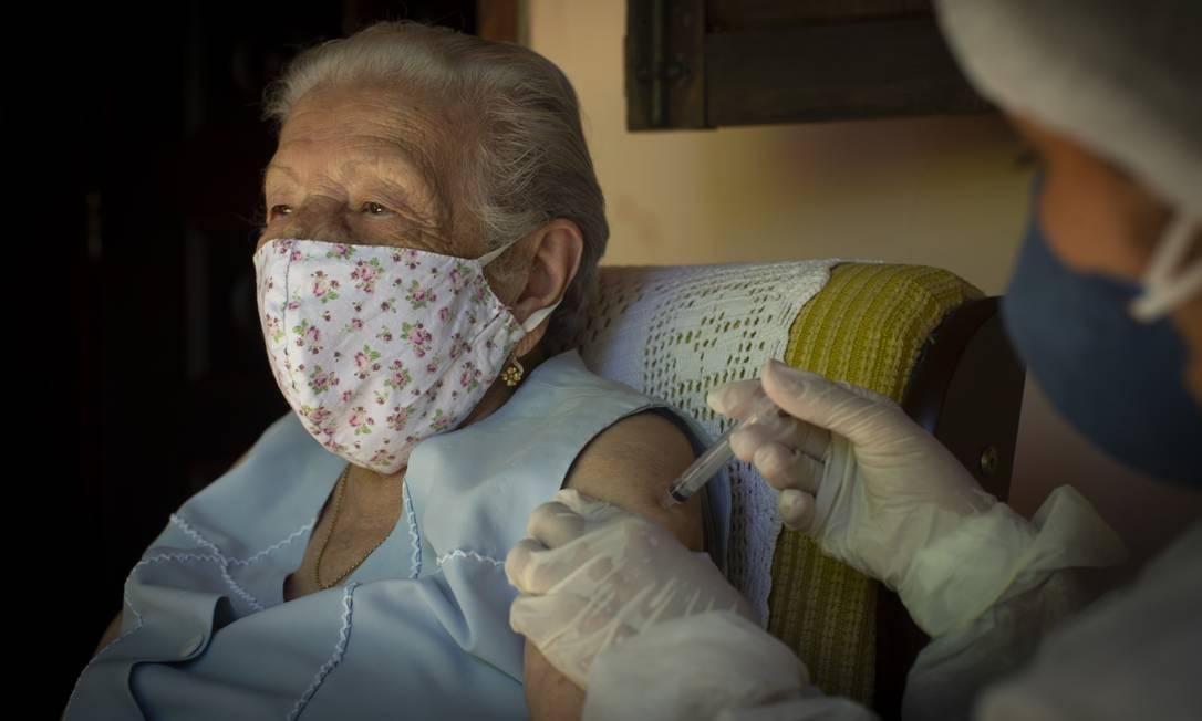 Maria José dos Santos Silva, de 100 anos, recebe a dose de Coronavac em casa, aplicada pela enfermeira Cristiane Moreira, no início da vacinação na cidade de Rio das Flores Foto: Márcia Foletto / Agência O Globo - 19/01/2021