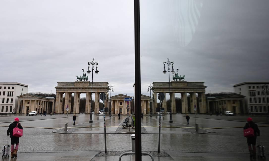 Pedestre caminha na Pariser Platz vazia diante dos Portão de Brandenburgo, com Berlim sob medidas restritivas contra a Covid-19, nesta sexta-feira (22) Foto: TOBIAS SCHWARZ / AFP