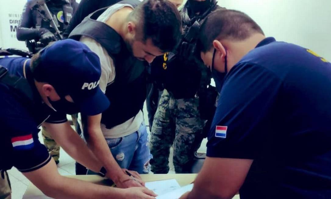 Traficante assina documentos antes de ser entregue às autoridades brasileiras em Foz do Iguaçu Foto: Divulgação