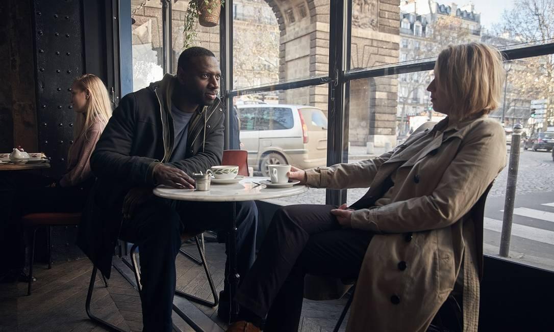 Omar Sy e Ludivine Sagnier numa cena de 'Lupin', da Netflix, com a Porte Saint-Martin, em Paris, ao fundo Foto: Emmanuel Guimier / Netflix / Divulgação