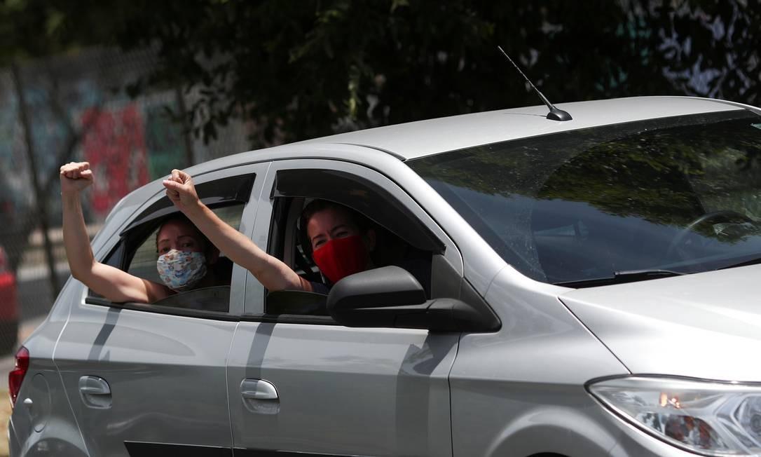 Ocupantes de um carro erguem o punho cerrado durante manifestação contra Jair Bolsonaro Foto: RICARDO MORAES / REUTERS