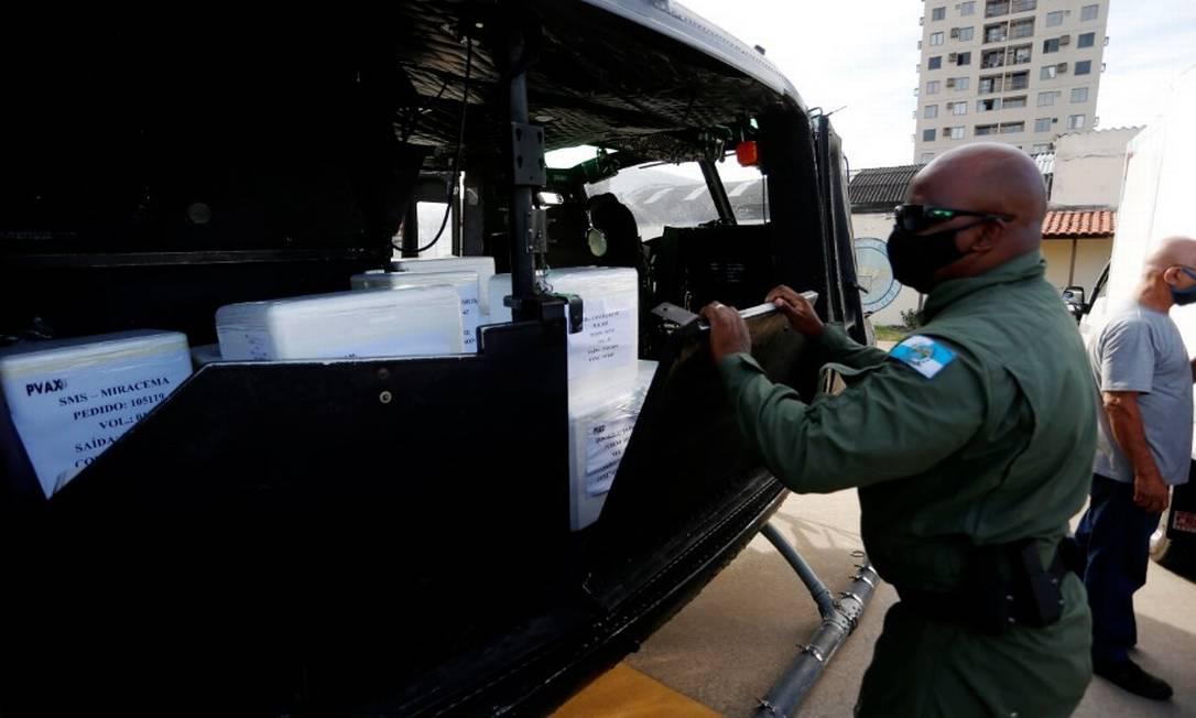 Policial organiza caixas com vacinas que serão levadas de helicóptero para o interior Foto: Fabiano Rocha / Agência O Globo