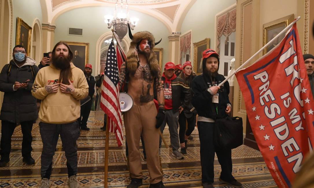 Apoiadores de Donald Trump, incluindo conspiracionistas e supremacistas brancos, durante invasão do Capitólio, no dia 6 de janeiro Foto: SAUL LOEB / AFP