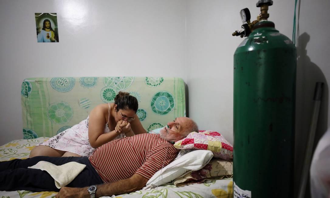 Osmar Magalhaes, 68, é assistido pela filha e por um cilindro de oxigênio em Manaus (AM) Foto: BRUNO KELLY / REUTERS