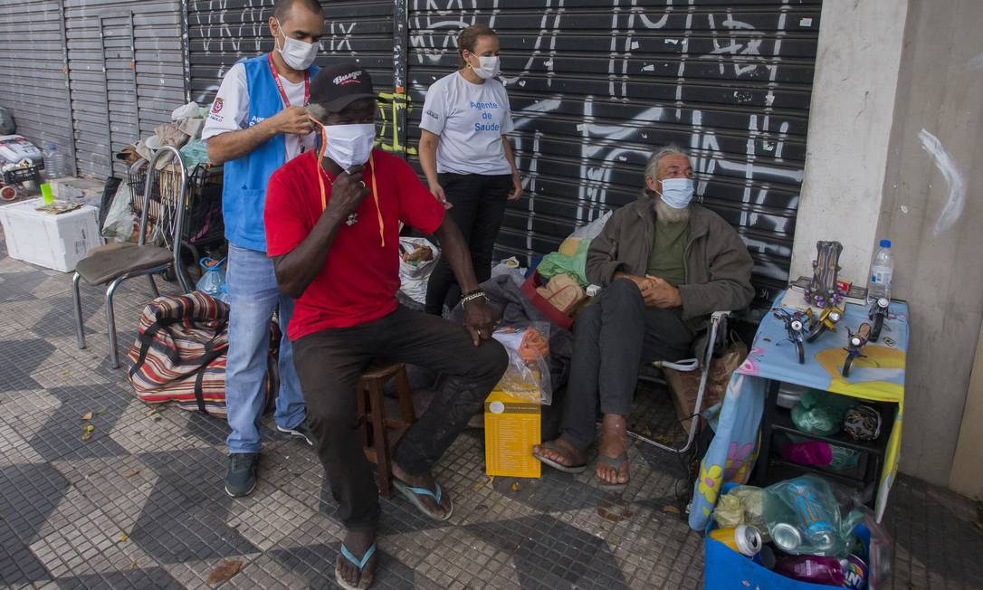 Osmar Alves e Wilson Da Hora são atendidos por agentes de saúde no bairro da Mooca, em São Paulo Foto: Edilson Dantas / Agência O Globo