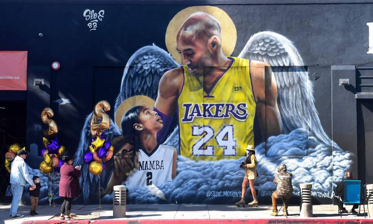 Pessoas se reúnem em frente a um mural do astro do basquete Kobe Bryant e sua filha Gianna, pintado pelo artista @Sloe_Motions em uma parede no centro de Los Angeles, Califórnia. Fãs marcam o aniversário de morte do atleta nesta-terça-feira (26) Foto: FREDERIC J. BROWN / AFP