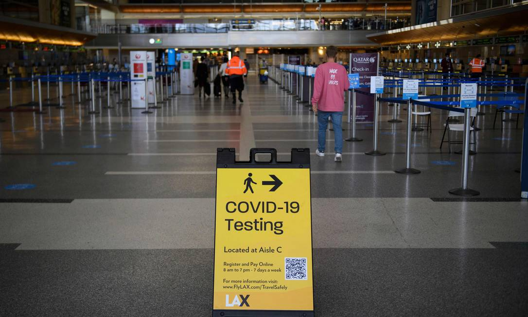 Sinalização de teste de Covid-19 é exibida nos balcões de check-in no Aeroporto Internacional de Los Angeles Foto: PATRICK T. FALLON / AFP/25-01-2021