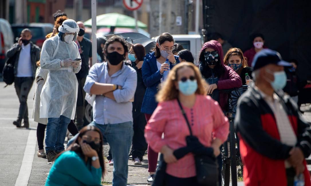 Pessoas usando máscara aguardam em fila para fazer o teste de Covid-19 em Bogotá, na Colômbia Foto: JUAN BARRETO / AFP/21-01-2021