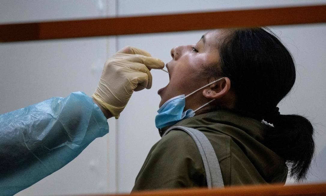 Residente passa por teste obrigatório de coronavírus, no distrito de Yau Tsim Mong de Kowloon, em Hong Kong, onde a China tenta controlar surto da Covid-19 na periferia densamente povoada Foto: ANTHONY WALLACE / AFP