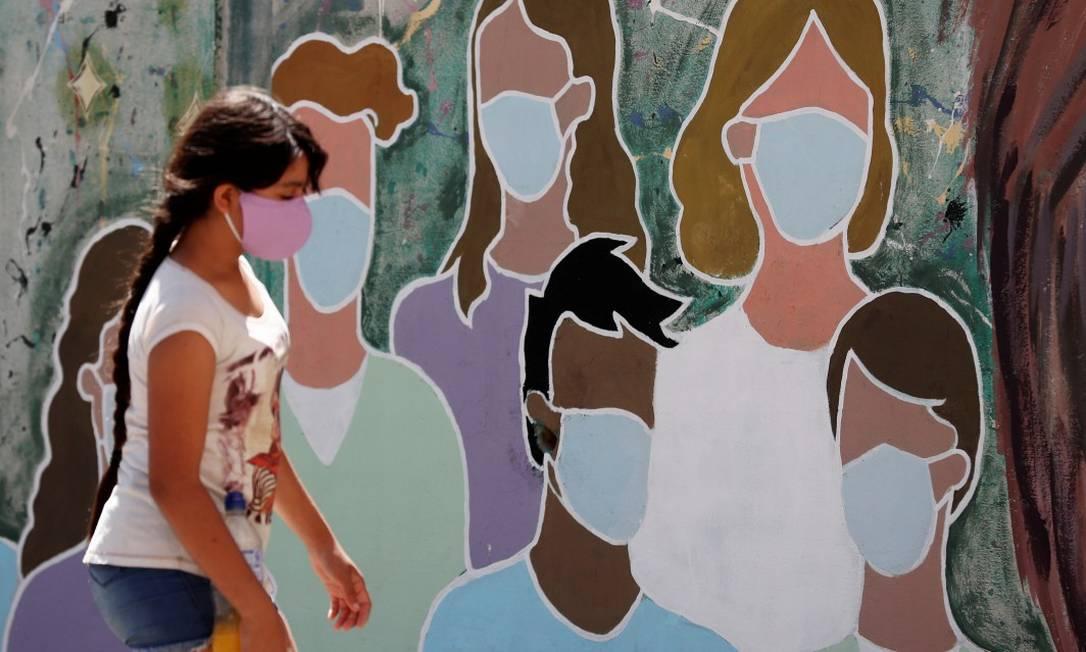 Em Buenos Aires, na Argentina, menina caminha em frente de mural com grafite de pessoas com máscaras Foto: AGUSTIN MARCARIAN / REUTERS