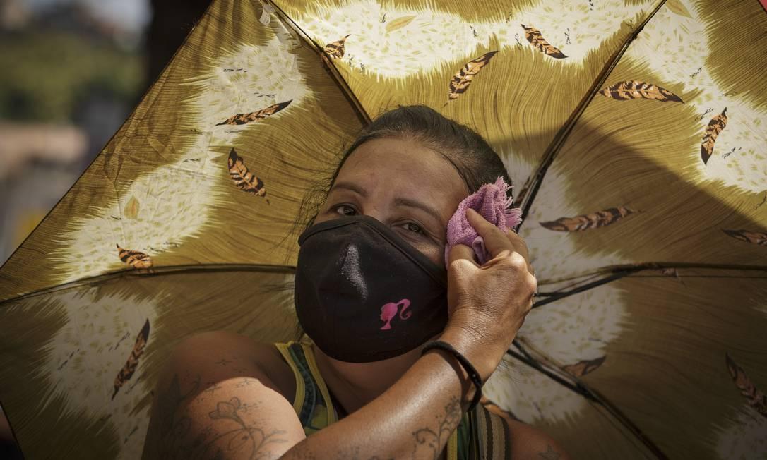 RI Rio de Janeiro (RJ) 28/01/2021 - Covid-19. A dificuldade de usar máscaras de proteção contra o coronavírus no verão cariosca. Na foto, Selma de Freitas, 54 anos, ambulante na Central do Brasil. Ela fica com uma sombrinha e uma toalha para limpar o suor, mas não tira a máscara. Foto de Márcia Foletto Foto: Márcia Foletto / Agência O Globo