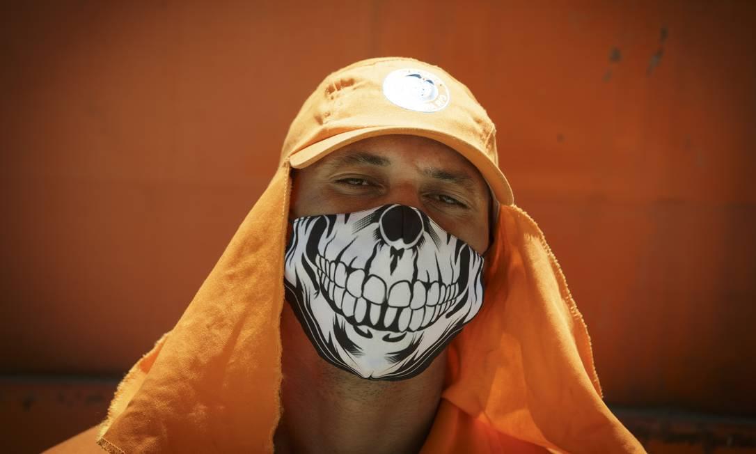 O gari Bruno Loureiro, 39 anos, conta que toma vários banhos por dia para refrescar e procura usar máscara com tecido mais fino para não sofrer tanto com o calor Foto: Márcia Foletto / Agência O Globo