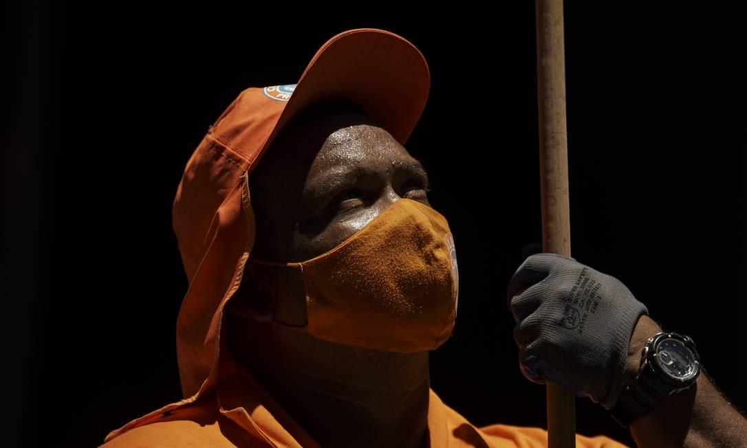 O gari Leandro Santos, 36 anos, diz que já se adaptou ao uso da máscara e carrega seis na bolsa para trocar durante o dia Foto: Márcia Foletto / Agência O Globo