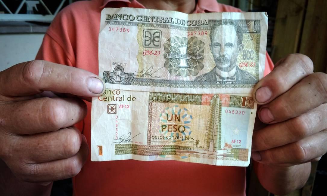 Morador de Havana mostra notas de um peso cubano e um peso conversível, as duas moedas que ainda circulam em Cuba Foto: Adalberto Roque / AFP