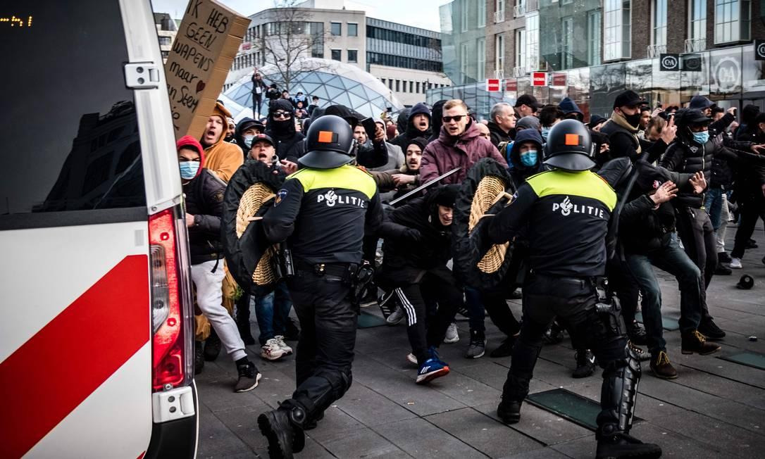 Manifestantes enfrentam policiais anti-motim holandeses durante uma manifestação contra as restrições ao coronavírus na praça 18 de setembro em Eindhoven, Holanda Foto: ROB ENGELAAR / AFP - 24/01/2021