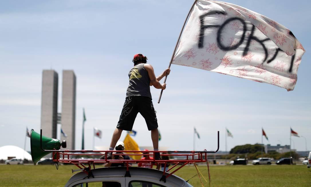 """Um manifestante agita uma bandeira em que se lê """"Fora"""" durante um protesto contra o presidente Jair Bolsonaro e sua gestão da crise da Covid-19 Foto: UESLEI MARCELINO / REUTERS"""