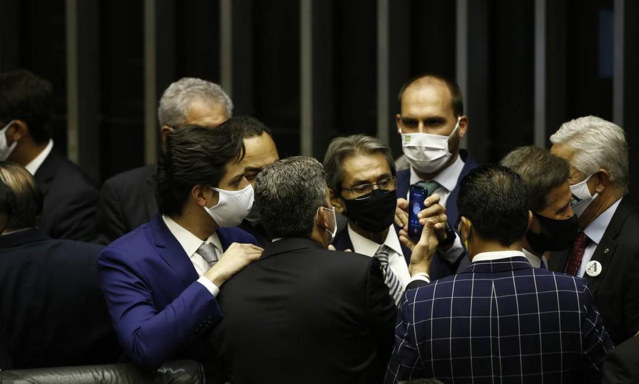 """Deputado Eduardo Bolsonaro (PSL-SP) passa o telefone para o recém-eleito presidente da Câmara, Arthur Lira (PP-AL). Na tela do aparelho lê-se """"JB OUT/2020"""". A eleição de Lira foi um alívio para o presidente que coleciona pedidos de impeachment que não entraram na pauta. Foto: Pablo Jacob / Agência O Globo - 01/02/2021"""