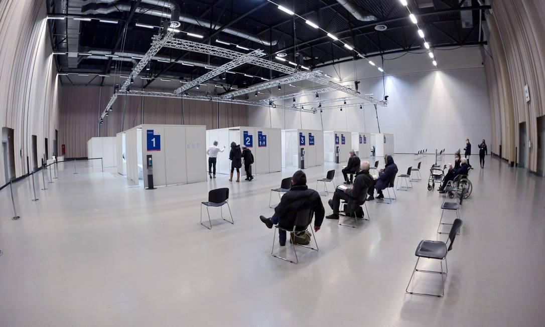Pessoas aguardam a vacinação contra COVID-19 em um centro instalado no salão Metropolishalle do Filmpark Babelsberg, em Potsdam, perto de Berlim, Alemanha Foto: SOEREN STACHE / AFP - 5/01/2021