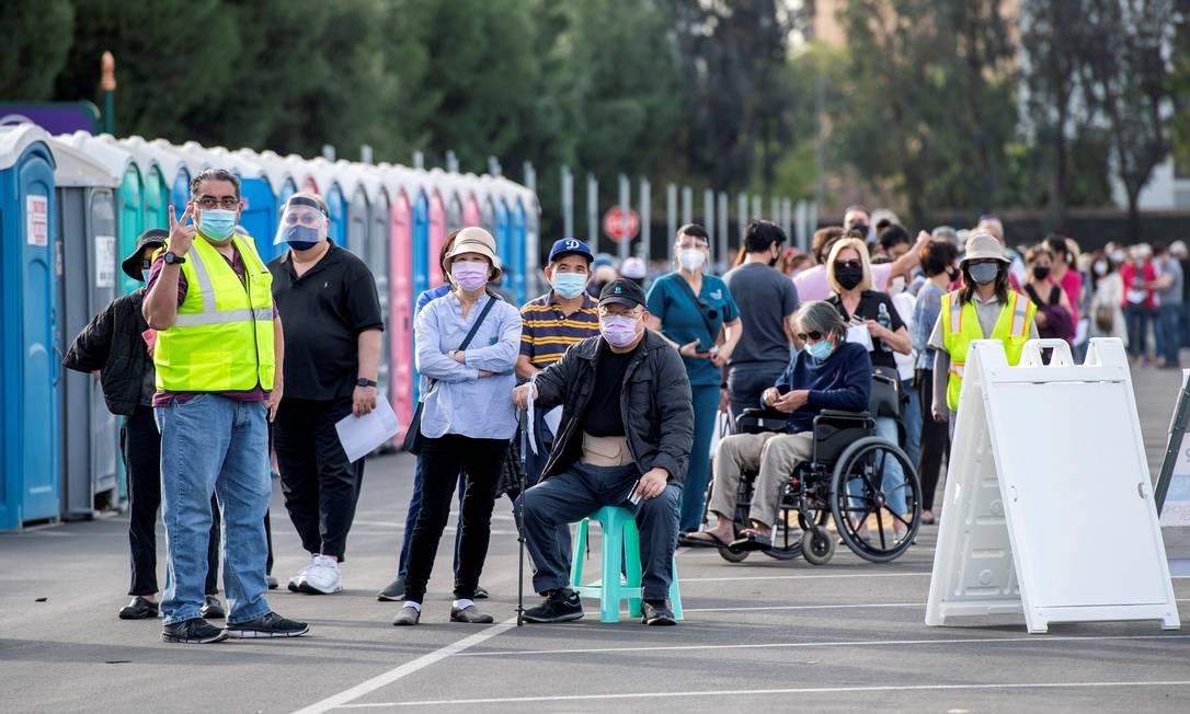 Pessoas esperam na fila em um estacionamento da Disneylândia para receber as vacinas contra a Covid-19 no parque temático, em Anaheim, Califórnia Foto: VALERIE MACON / AFP - 14/01/2021