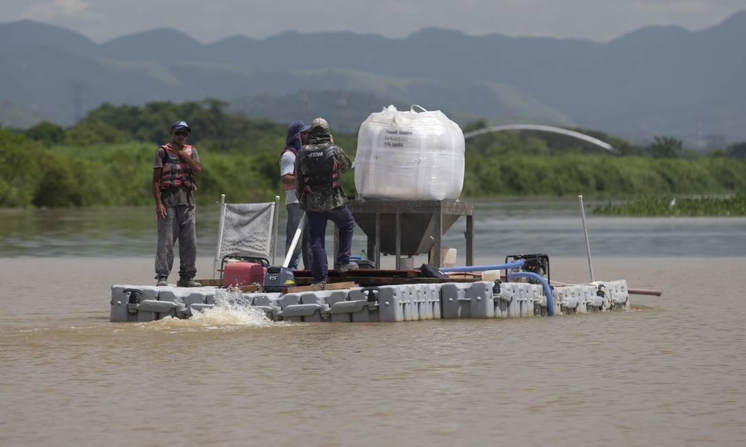 Balsa da Cedae joga produtos na água do lagoão de captação de água do Rio Guandu, em Nova Iguaçu Foto: Márcia Foletto