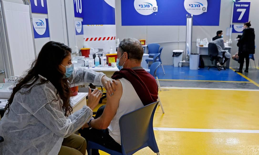 Profissional de saúde do centro de vacinação de Maccabi administra uma dose da vacina contra o coronavírus da Pfizer/BioNtech, na cidade costeira de Tel Aviv, em Israel, em janeiro de 2021. Foto: JACK GUEZ / AFP