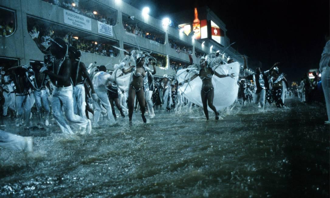 """Com água na altura da canela, os componentes da Beija-Flor cruzaram a Avenida em meio a um dilúvio no desfile """"O mundo é uma bola"""" (1986) Foto: Otávio Magalhães / Agência O Globo - 10.02.1986"""
