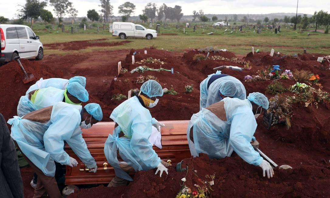 Trabalhadores funerários carregam caixão de vítima da Covid-19 em Joburg, na África do Sul Foto: Siphiwe Sibeko / REUTERS
