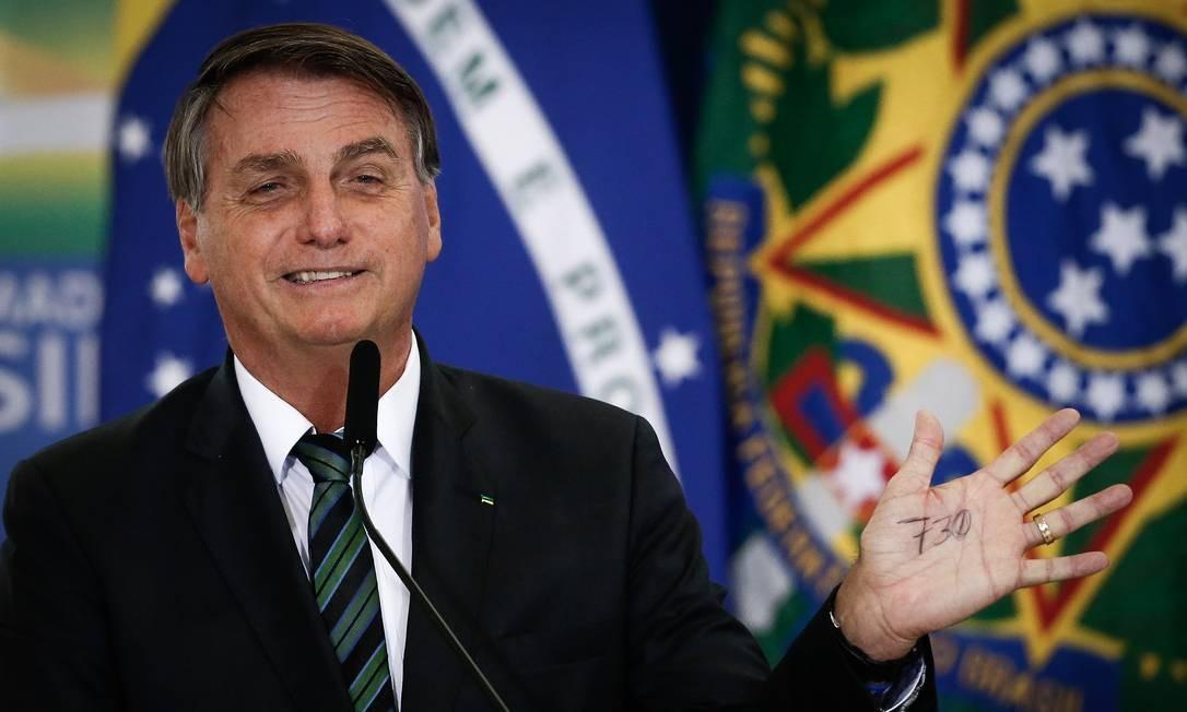 O presidente Jair Bolsonaro mostra anotação na mão com o tamanho da fronteira da Guiana Francesa com o Brasil, durante cerimônia no Palácio do Planalto Foto: Pablo Jacob/Agência O Globo